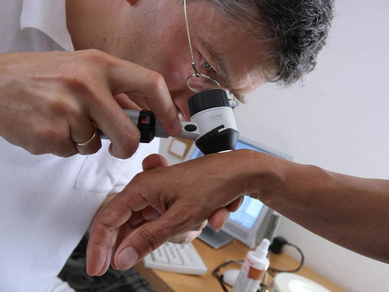 обследует кожу